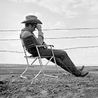 James Dean Seated Behind Fence on Set of 'Giant'
